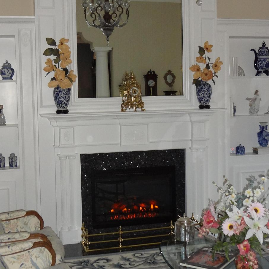 A colonial style fireplace mantel painted white